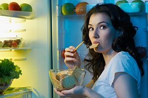 woman eating snacks in front of the open fridge